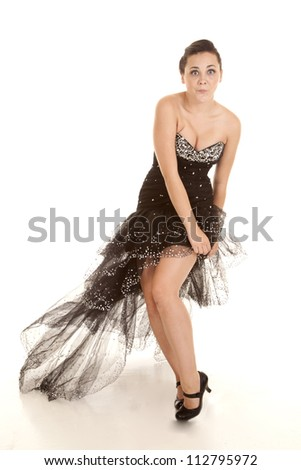 A woman with  a funny expression on her face holding down her dress in the wind. - stock photo