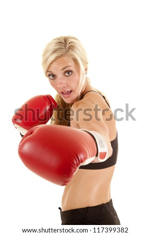 A woman with a funny expression on her face punching towards the camera. - stock photo