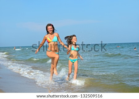 A woman with a little girl running on the beach