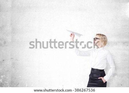 A woman with a paper plane ready to let it go. Side view. Concrete background. Concept of starting a new project. - stock photo