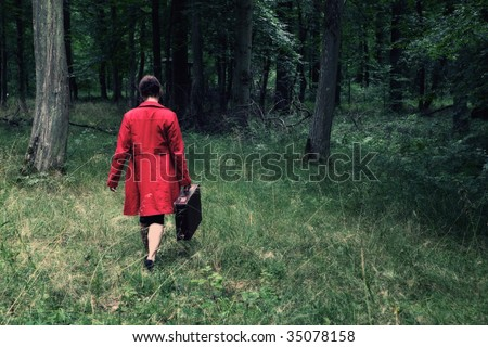 A woman with a red coat and a case is walking in the forest
