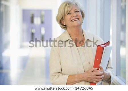 A woman with a ringbinder standing in a campus corridor - stock photo