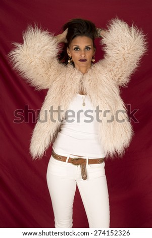 a woman with a sensual expression on her face, wearing her fur coat with her hands in her hair. - stock photo