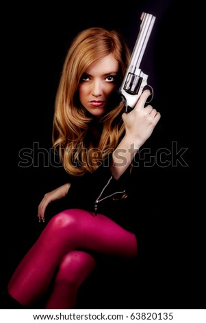 A woman with a serious expression on her face holding a gun next to her face. - stock photo