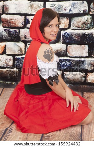 A woman with a serious expression on her face in her red hood showing off her wolf paw print on her shoulder. - stock photo