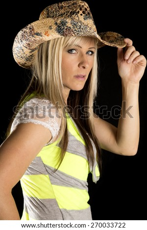a woman with a serious expression on her face in her western hat. - stock photo