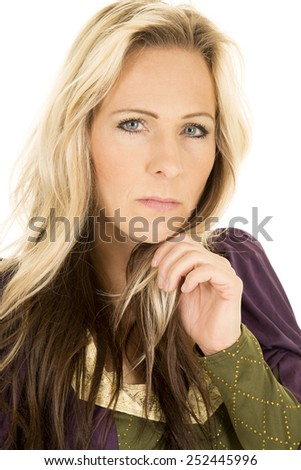 a woman with a serious expression on her face with her hand under her chin. - stock photo