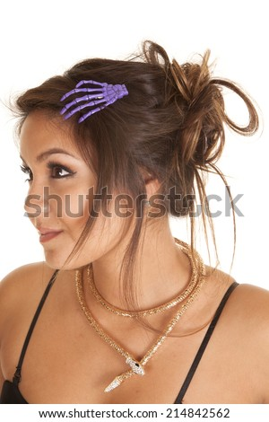 A woman with a skeleton hand in her hair and a snake necklace around her neck, looking to the side. - stock photo