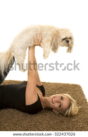a woman with a smile on her face, holding up her puppy in the air. - stock photo