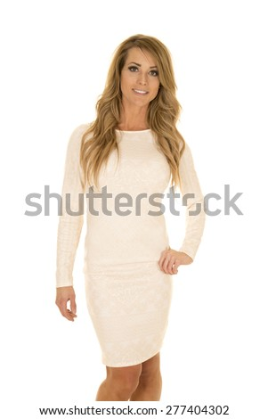 A woman with a smile on her face, in her white fitted dress. - stock photo