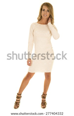 A woman with a smile on her face in her white fitted dress.