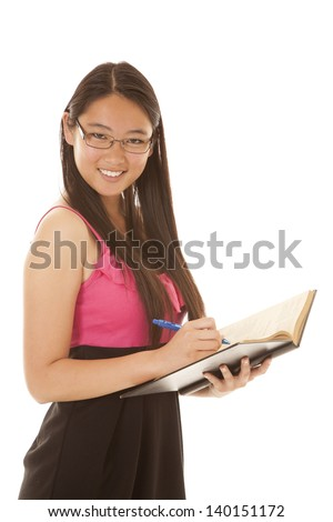 A woman with a smile on her face looking in her book.