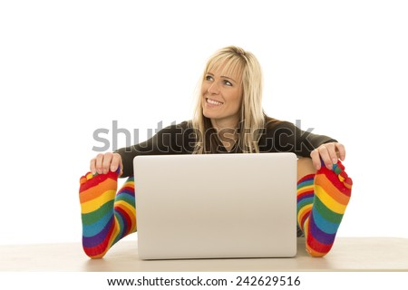 a woman with a smile on her face looking to the side touching her toes by her laptop.