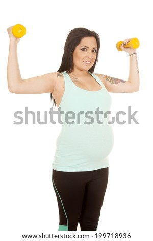 A woman with a smile on her face using weights to work out.