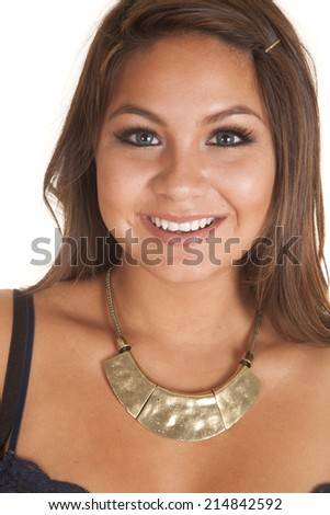 A woman with a smile on her face, wearing a gold necklace around her neck. - stock photo