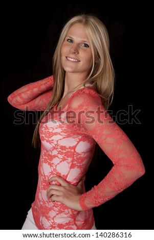 A woman with a smile on her lips in her red lace top. - stock photo