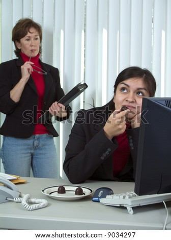 A woman with an annoyed look on her face observing another dreamily enjoying chocolate candy. - stock photo