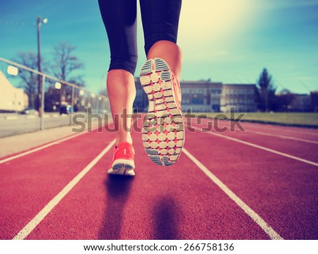 a woman with an athletic pair of legs going for a jog or run during sunrise or sunset - healthy lifestyle concept toned with a retro vintage instagram filter effect app or action - stock photo