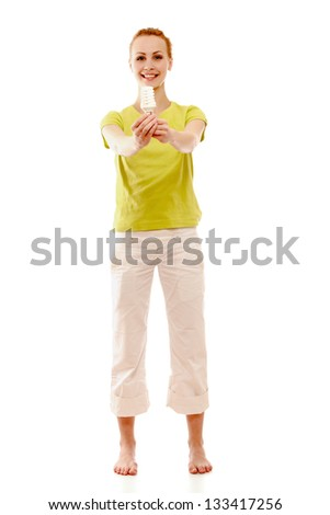 A woman with an energy-saving bulb in her hands, a full-length portrait - stock photo