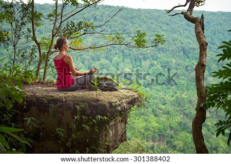 A woman with backpack sitting on the cliff and relaxing high in mountains on the background of sunrise.Traveling along Asia, active lifestyle concept - stock photo