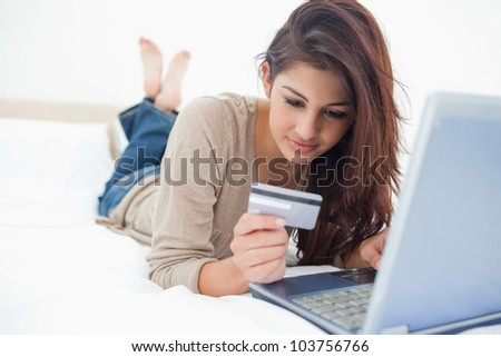A woman with crossed legs lying on the bed looking at her credit card details in front of her laptop. - stock photo
