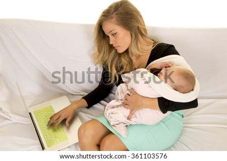 a woman with her baby in her arms working on her laptop.