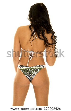 a woman with her back to the camera, in her green bikini. - stock photo
