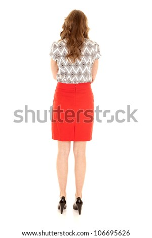 A woman with her back to the camera in her red skirt and black shoes. - stock photo
