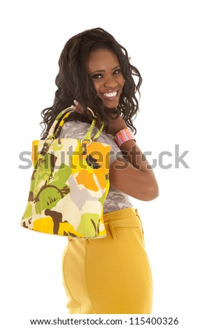 a woman with her bag over her shoulder looking over her shoulder with a smile on her lips. - stock photo