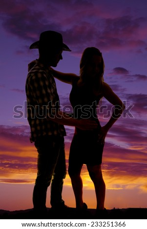 a woman with her cowboy in a silhouette together in each others arms. - stock photo