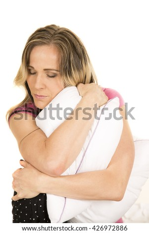 A woman with her eyes closed hugging on her pillow. - stock photo