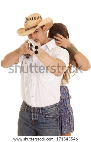 a woman with her eyes covered as her cowboy is getting ready to shoot. - stock photo