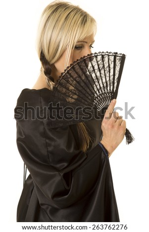 a woman with her face hidden by a black fan. - stock photo