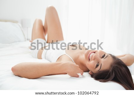 A woman with her hair flowing down the edge of the bed as she smiles with her hands to the sides of her head and her knees slightly raised. - stock photo