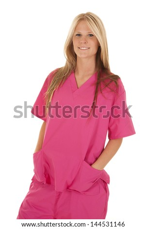 A woman with her hands in her scrubs pocket with a smile on her face. - stock photo