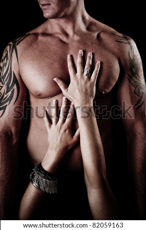 A Woman with her hands on a Sexy Muscular Chest of a Man - stock photo
