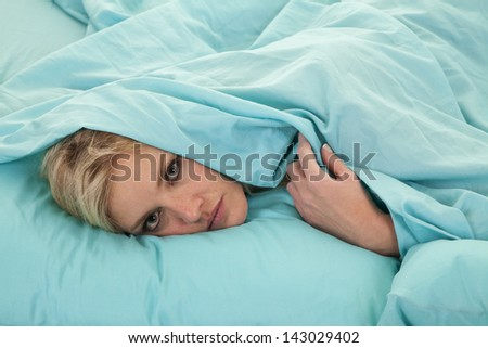 a woman with her head covered by her sheet peeking out from underneath her sheet.
