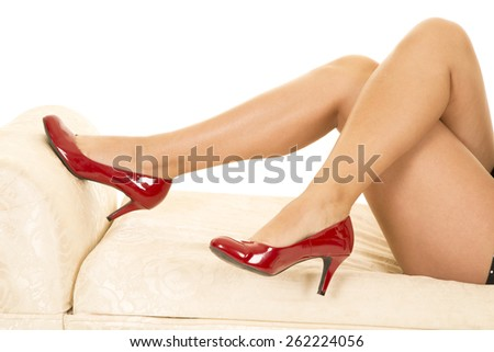 a woman with her legs crossed in her red heel shoes. - stock photo