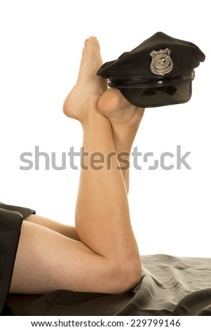 A woman with her legs up and a police hat on her feet. - stock photo