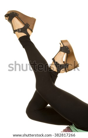 a woman with her legs up in her black leggins with shoes. - stock photo
