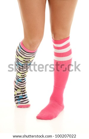 A woman with non matching socks on her feet and legs. - stock photo