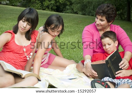 A woman with three teens or preteens sitting outside as if engaged in bible study.