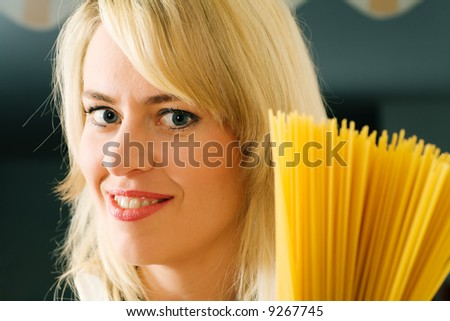 A woman with uncooked spaghetti (focus is on her face) - stock photo