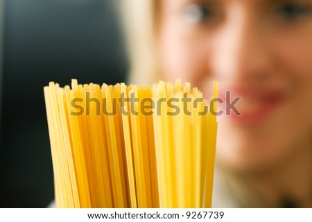 A woman with uncooked spaghetti (focus is on the spaghetti) - stock photo