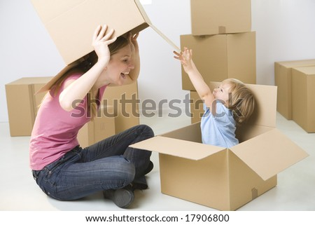 A woman with young girl sitting between cardboard boxes. Happy woman holding box over head and looking at young girl. Young girl sitting in box. - stock photo