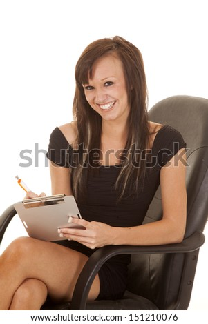 A woman working and sitting in a chair with a smile on hr face taking notes.