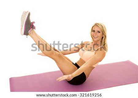 a woman working out doing a crunch with a smile. - stock photo