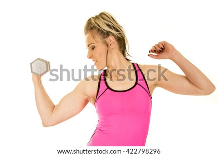 A woman working out her arm doing a curl looking at her bicep. - stock photo
