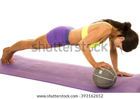 a woman working out her body by doing a push up with one hand on a medicine ball.