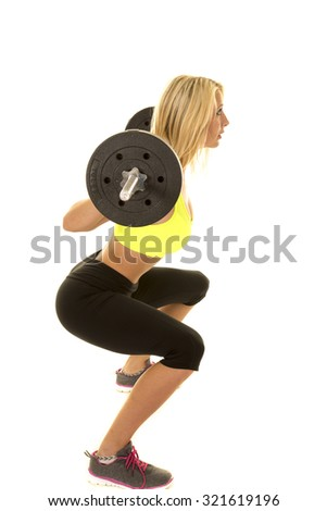 A woman working out with a bar doing a squat.